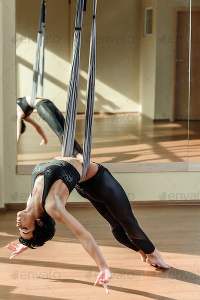 young athletic woman hanging relaxed on aerial silk while practicing fly yoga in front of mirror