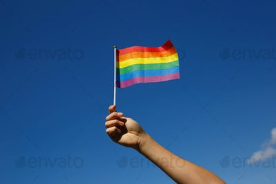 small lgbt flag in the hand against the blue sky