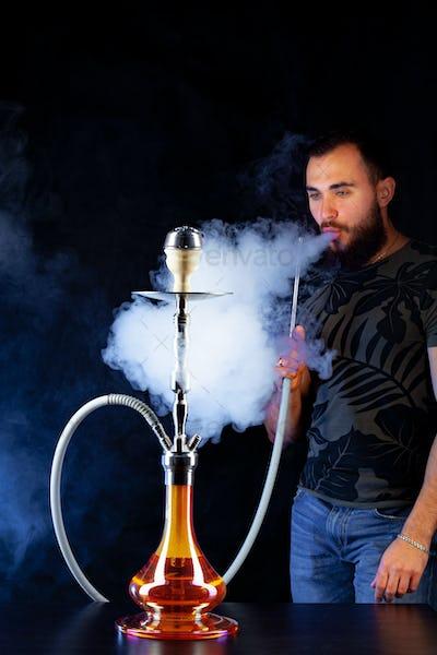 Bearded young man smoking shisha in a dark night club