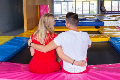 Man and woman sits together on a trampoline indoors.