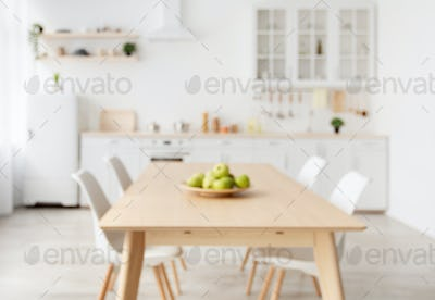 Blurred background with modern light kitchen, wooden dining table and white furniture, chairs