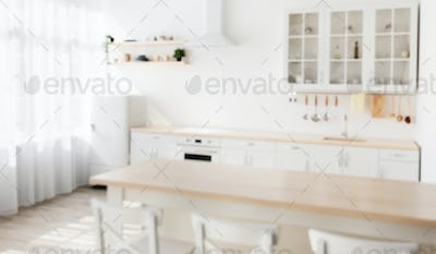Defocused photo of wooden dining table and white chairs nearby, various utensils on light kitchen