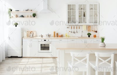 Light kitchen furniture after renovation. Kitchenware and plants on shelves, chairs and table in