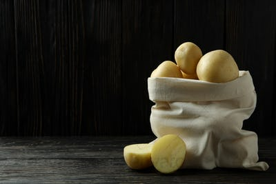Bag of young potato on wooden table