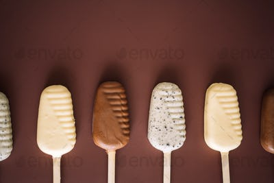 Line of milk and white chocolate popsicles on brown background, top view