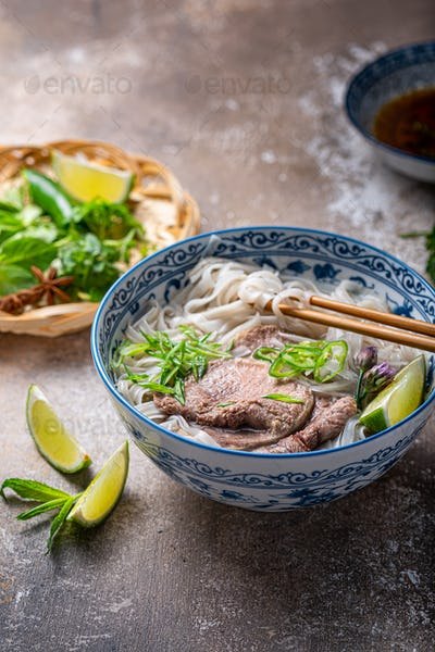 Close view of pho bo in traditional bowl, garnished with basil, mint, lime, on concrete background