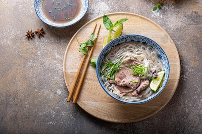 Top view of pho bo vietnamese rice noodle soup with herbs and sauce