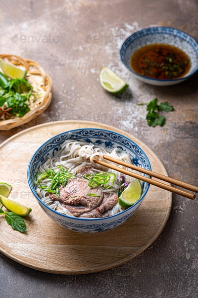 Traditional vietnamese noodle soup pho in bowl, garnished with basil, mint, lime, on concrete