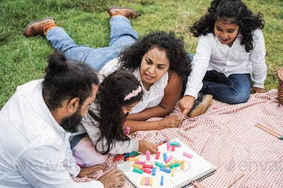 Indian parents having fun at city park playing with wood toys with their daughter and son