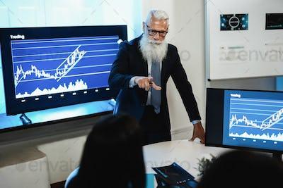 Multi generational trader team making stock market analysis conference - Focus on senior man face