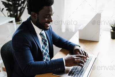 Business african man working inside modern office using computer laptop - Focus on face