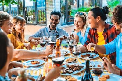 Group of friends having fun at bbq dinner outdoor in garden restaurant