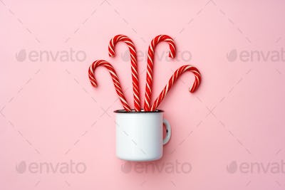 Candy canes on pink background top view