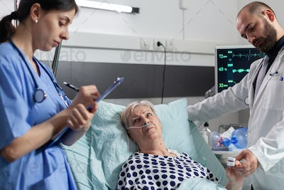 Sick senior woman looking at medical staff laying in hospital bed