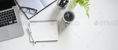 Top view white workspace is surrounding by a coffee cup and various equipment.