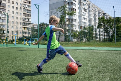 Little boy in blue and green form playing football on open field in the yard, a young soccer player