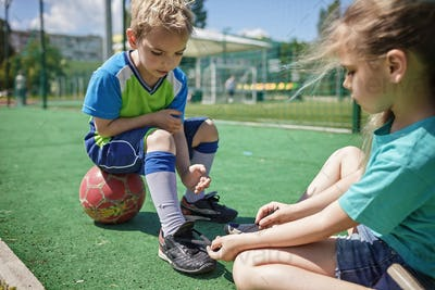 Older sister ties laces on boots to his brother during game on football field, fan support, sports