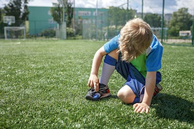 Young soccer player looks at the boots torn during the game on football field, hard training, sport