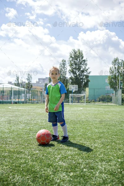 Sweaty focused little soccer player during match on football field, real fan and future champion