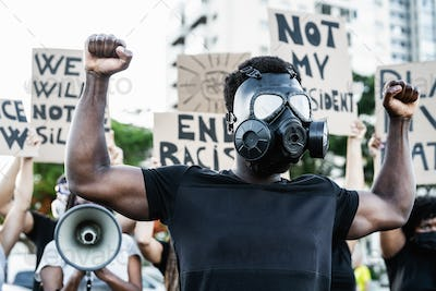 Activist wearing gas mask protesting against racism and fighting for equality