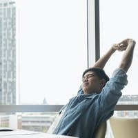 Young businessman is relaxing in office and  stretching his body