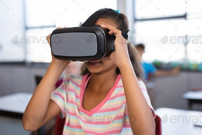 African american girl wearing vr headset while sitting on her desk in the class at school