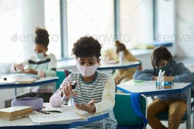 Boy Sanitizing Hands in Classroom