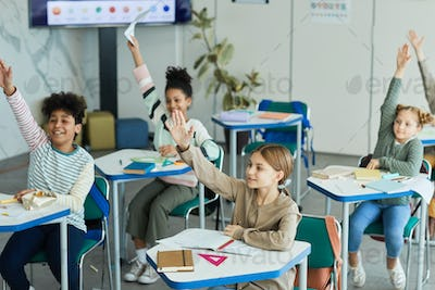 Excited Kids Raising Hands in Class