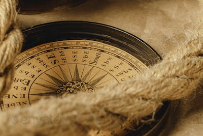 Ship rope and compass on wooden background