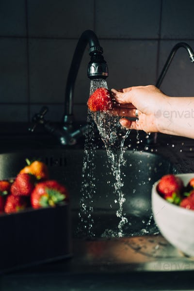 Woman hands washing fresh ripe strawberries in the kitchen. Red vibrant strawberries under water