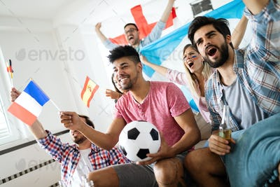 Cheerful and happy group of friends watching olympic games on tv