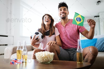 Young couple sport fans watching match on television at home