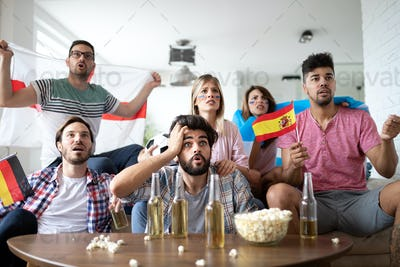 Shocked, frustrated friends watching football game at home
