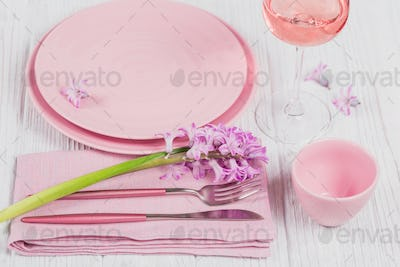 Pink rustic table setting with purple hyacinth flowers, linen napkin and glass of rose wine
