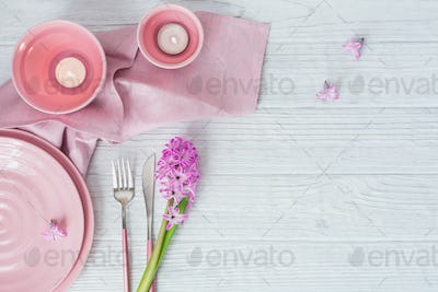 Pink rustic table setting with purple hyacinth flowers