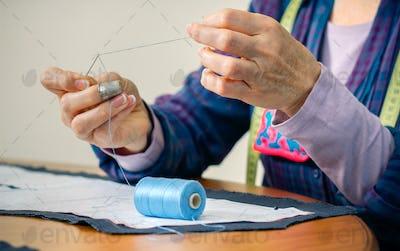 Senior female dressmaker threading a needle