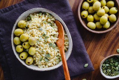 Bulgur with green olives and pepitas, healthy nutrition easy recipe from long-stored food.