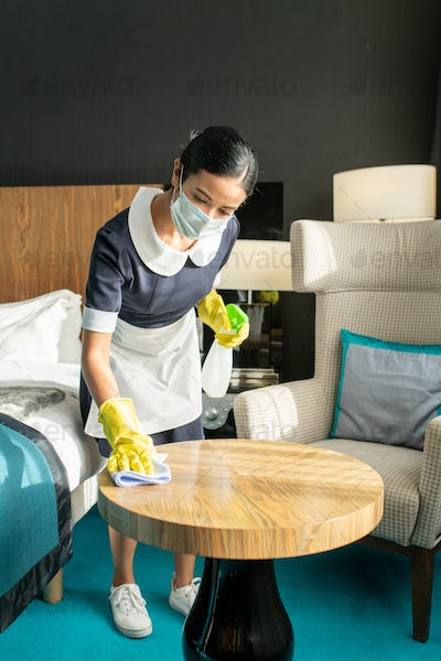 Young female in protective mask and uniform cleaning table