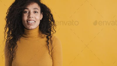 Close up smiling African American woman with dark curly hair smi