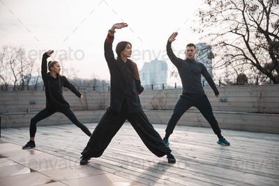Tai chi teacher with students working out on the roof