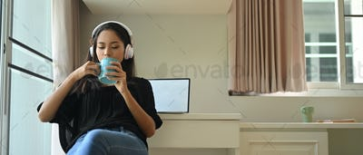 A young woman with the headphone is drinking a coffee in the comfortable living room.