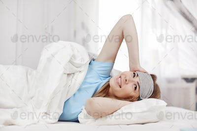Cute girl in a sleep mask lies in bed and stretches after waking up.