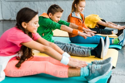 Kids in bright clothes stretching on fitness mats