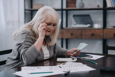 senior woman sitting at table with paperwork, holding glasses and counting money