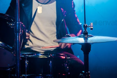 cropped image of male musician playing drums during rock concert on stage with smoke and dramatic