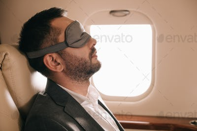 side view of businessman in sleeping mask sitting in private jet
