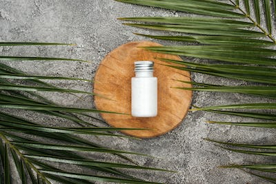 top view of wooden board with coconut cream near green palm leaves on grey textured background