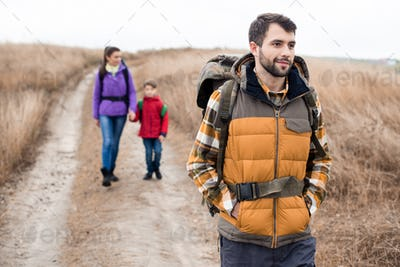 Close-up portrait of young man with wife and son backpacking in rural area at cloudy autumn day
