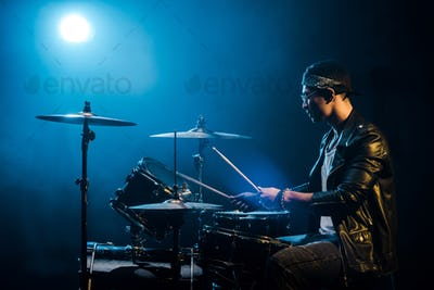 side view male musician in leather jacket playing drums during rock concert on stage with smoke and