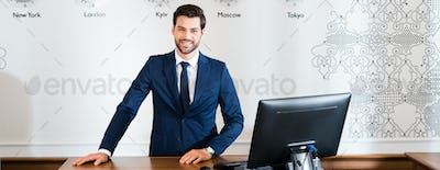 panoramic shot of happy receptionist standing at reception desk in hotel